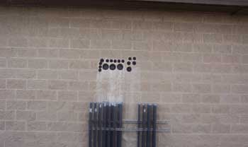 Markings on a wall above pipes
