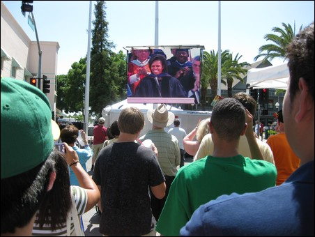 Crowd viewing the commencement speech on a screen
