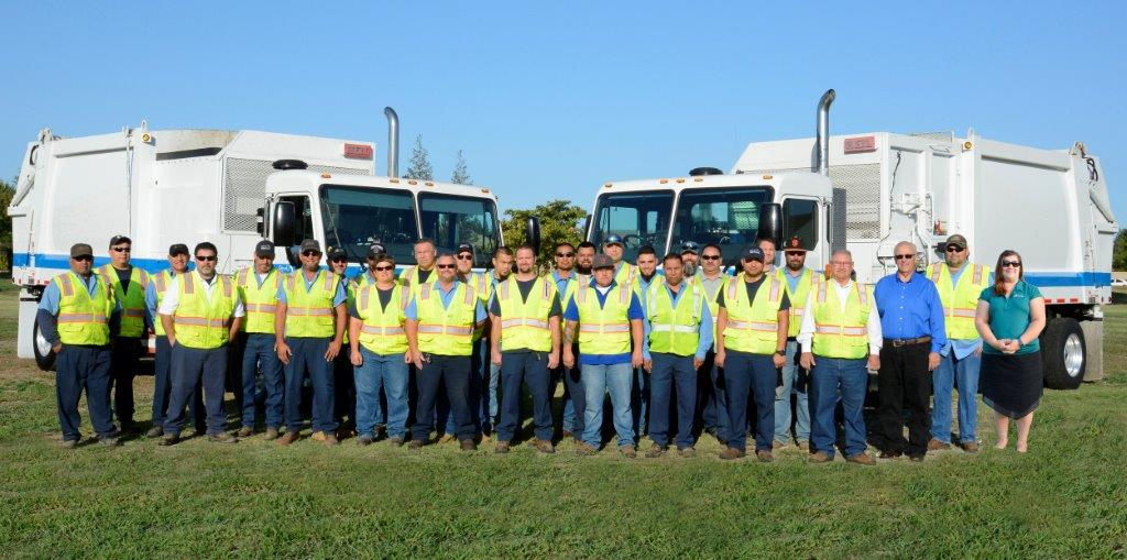 Refuse Division workers in front of trucks