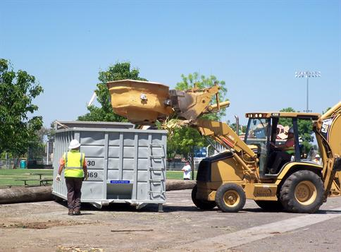 Trash being loaded into a large dumpster